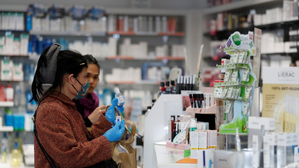 Two women try to buy sanitiser in a shop in Milan