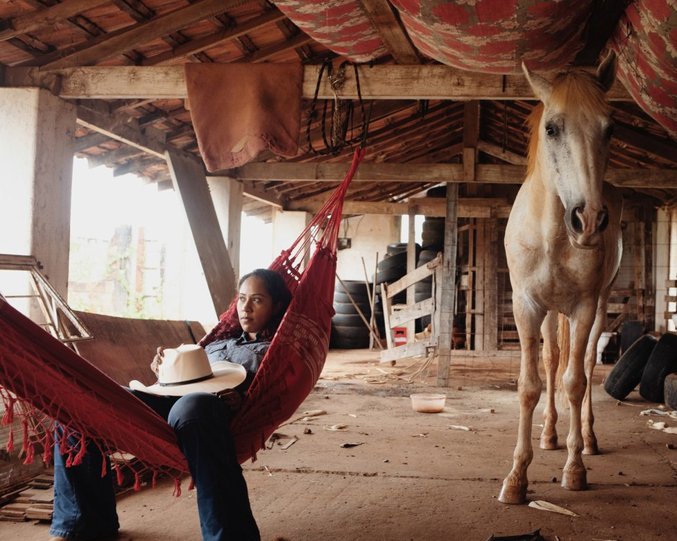 A woman lying in a hammock next to a horse