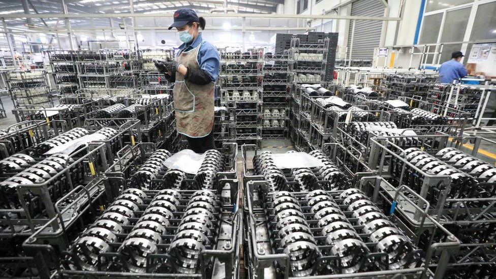 An employee works on the production line of gear wheel at a factory of Zhejiang Shuanghuan Driveline.