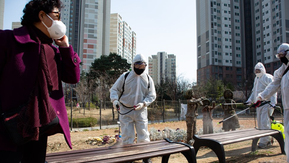 Local residents spray disinfectant in their neighbourhood as a precaution against the coronavirus outbreak, in Seoul, South Korea, 23 March 2020