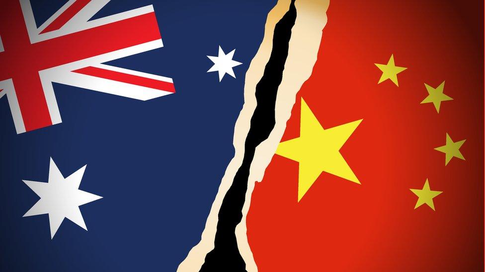 Banderas de Australia y China rasgadas.