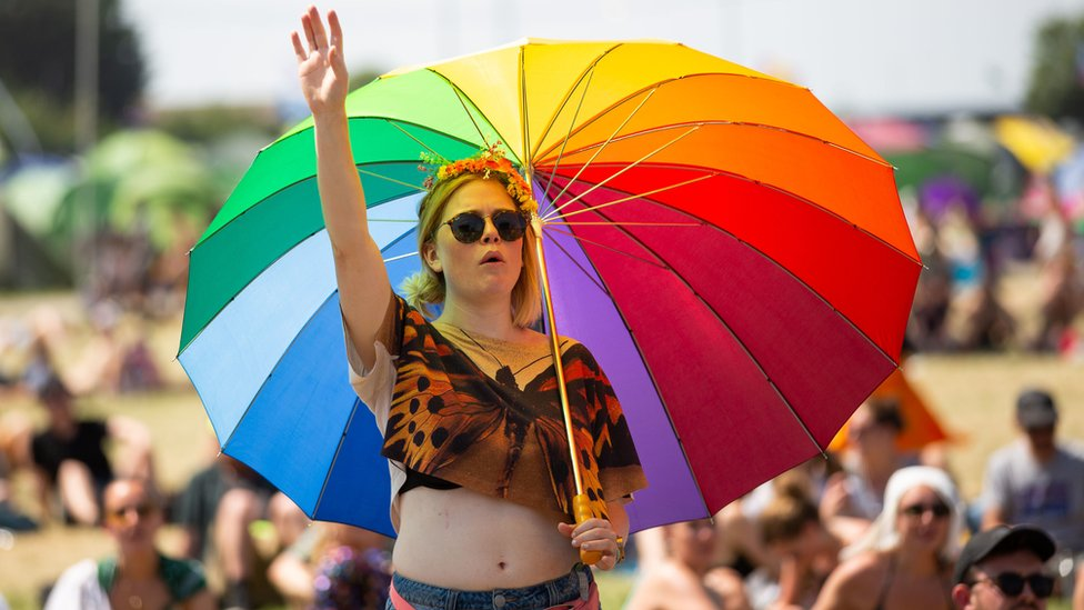 A festival goer in the sun at Glastonbury Festival at Worthy Farm in Pilton, Somerset.