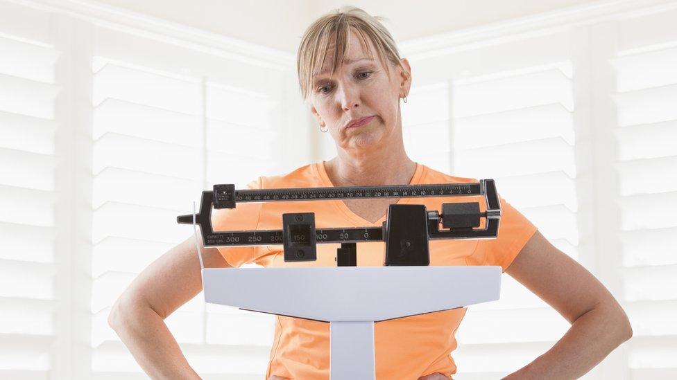 Un mujer mira su peso en una báscula