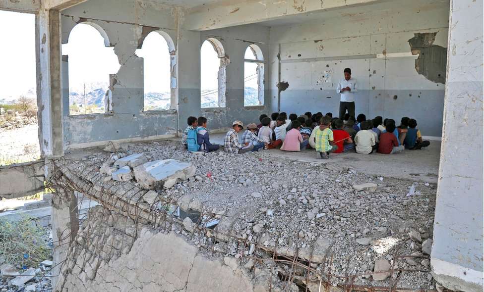 Yemeni children attend class in a badly damaged school building