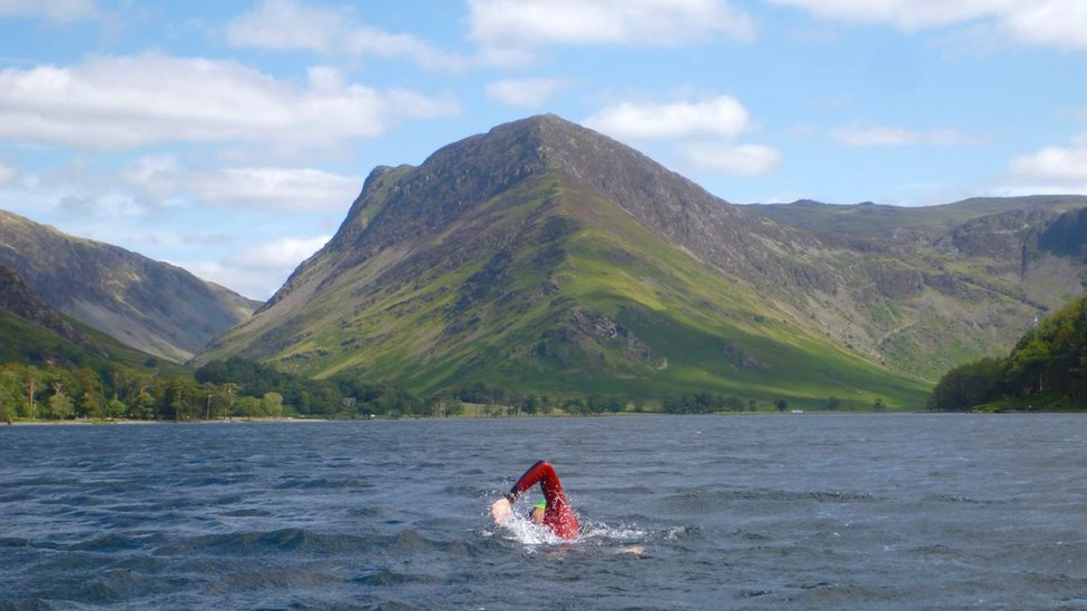 George Taplin swims in front of large hill