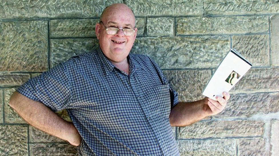 Les Murray stood outside, wearing glasses, smiling, holding an book, looking at the camera