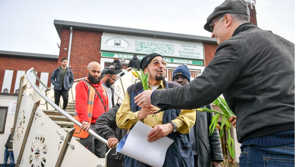 A man hands out flowers to Muslims as they leave Birmingham Central Mosque as Friday prayers finish