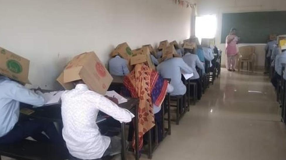 طلاب تغطي رؤوسهم صناديق من الورق المقوى