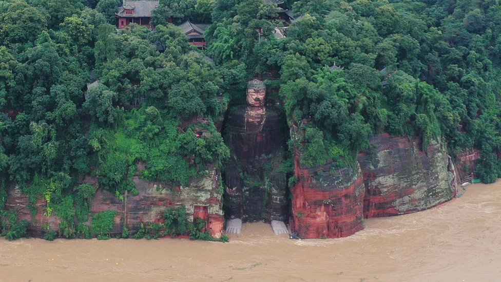 Giant Buddha carved from rock with floodwater around its base (18 Aug)