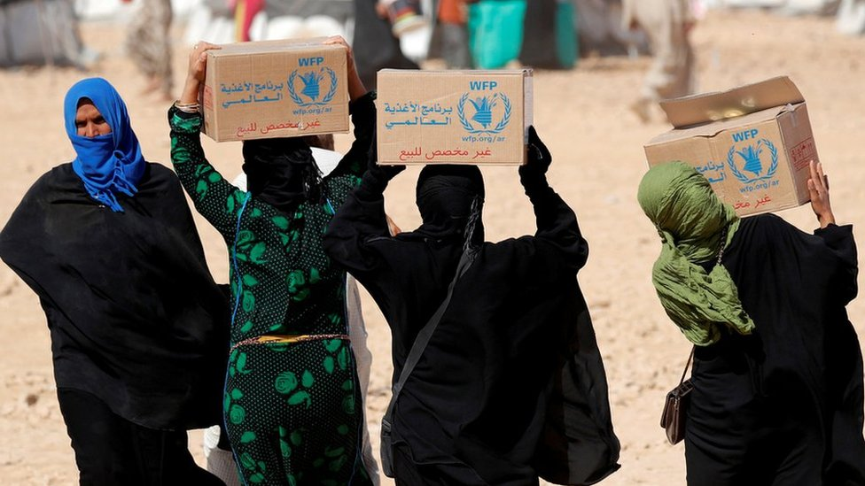 People carry boxes of food aid given by UN's World Food Programme at a refugee camp in Ain Issa, Syria