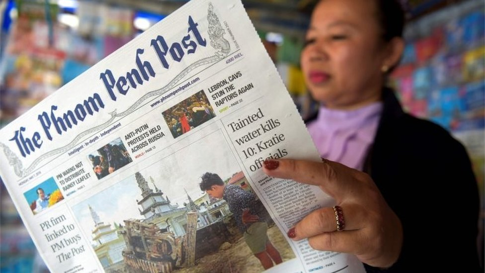 """A Cambodian vendor reads the Phnom Penh Post newspaper at her newstand in Phnom Penh on May 7, 2018. The newspaper hailed as Cambodia""""s last independent English daily has been sold to a Malaysian investor with apparent business links to premier Hun Sen, rattling a journalist community that has been battered by the strongman ahead of elections."""