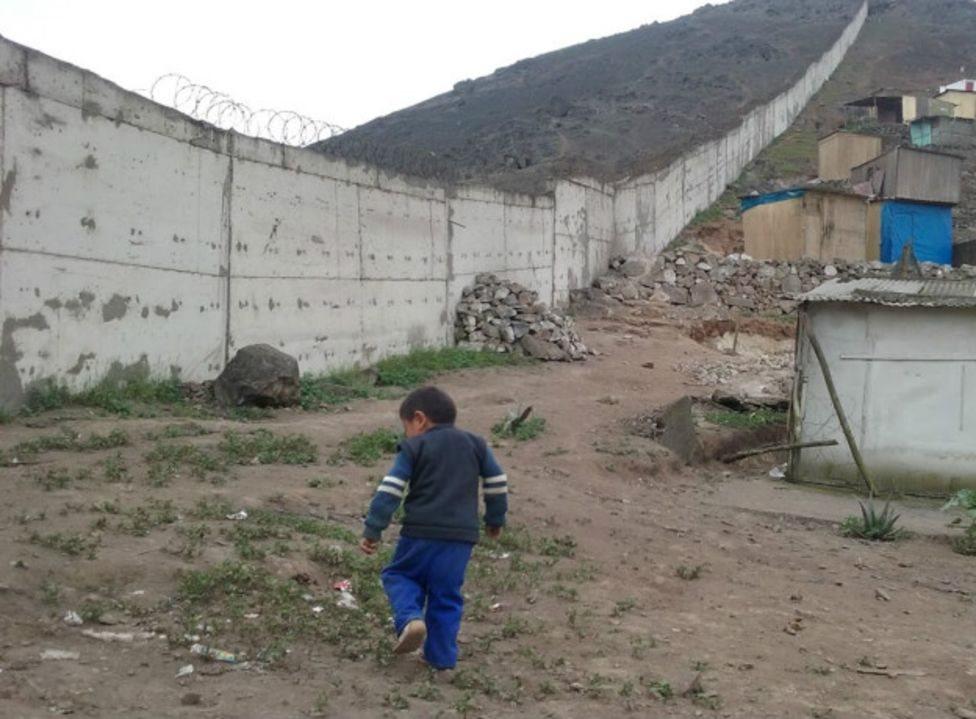 Niño caminando en una villa miseria