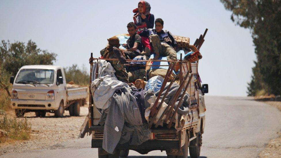 Displaced Syrians sit on a van moving through rebel-held Deraa province (26 June 2018)