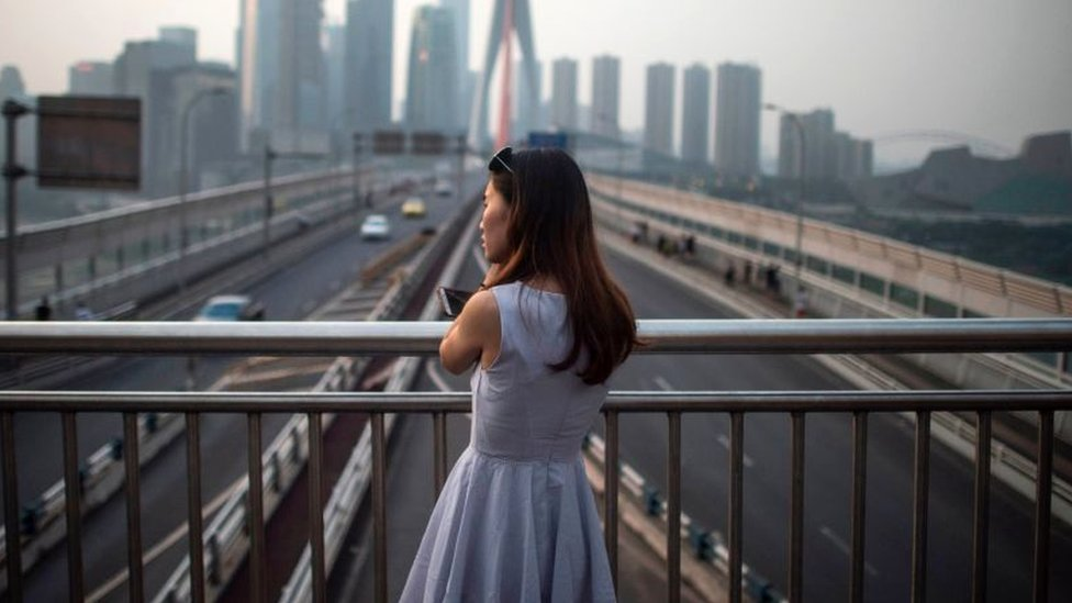 A young lady enjoys the view of the Yangtze river in Chongqing on May 31, 2017