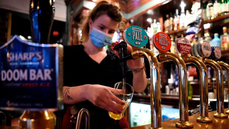 A woman pours a pint in a pub in Mayfair, London