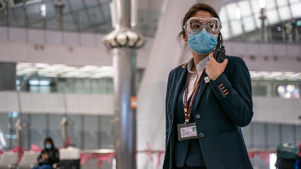 Una empleada del aeropuerto de Hong Kong usando una mascarilla.