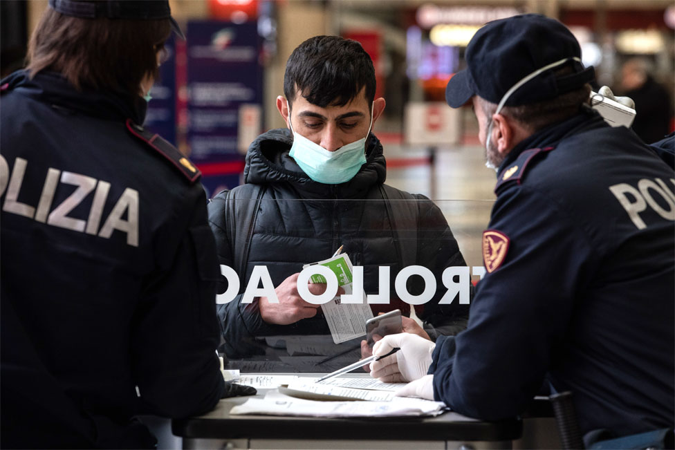 Italian State Police officers speak to man