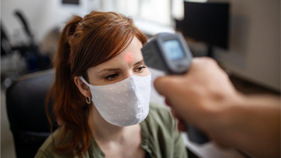 Un termómetro electrónico registra la temperatura de una empleada