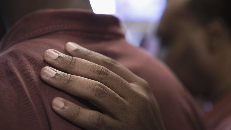 Una mano de un hombre en la espalda de otro en señal de apoyo.