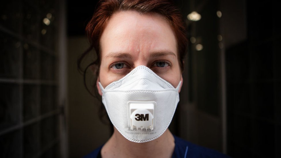 A Spanish healthcare worker wears a mask