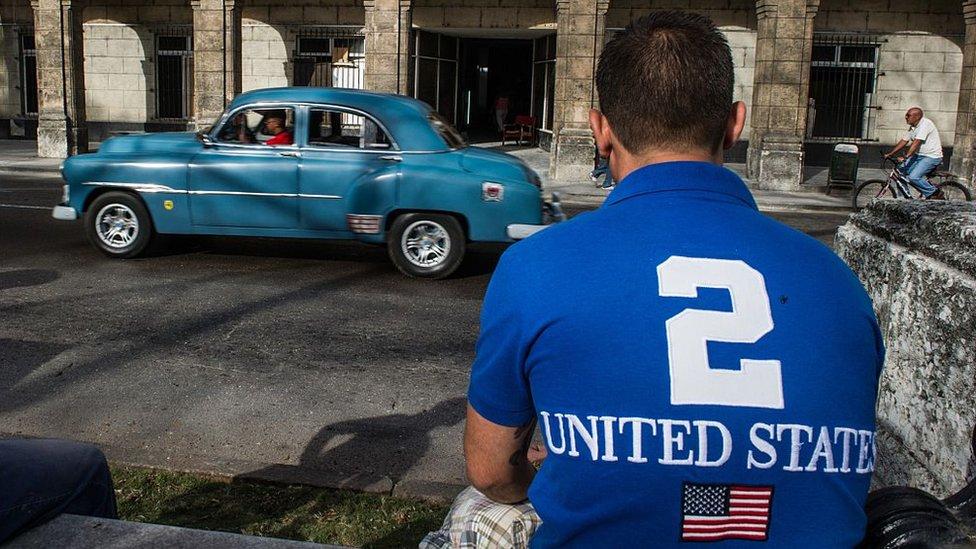 Un hombre de espaldas con una camiseta de Estados Unidos (en inglés) y la bandera de ese país en Cuba.