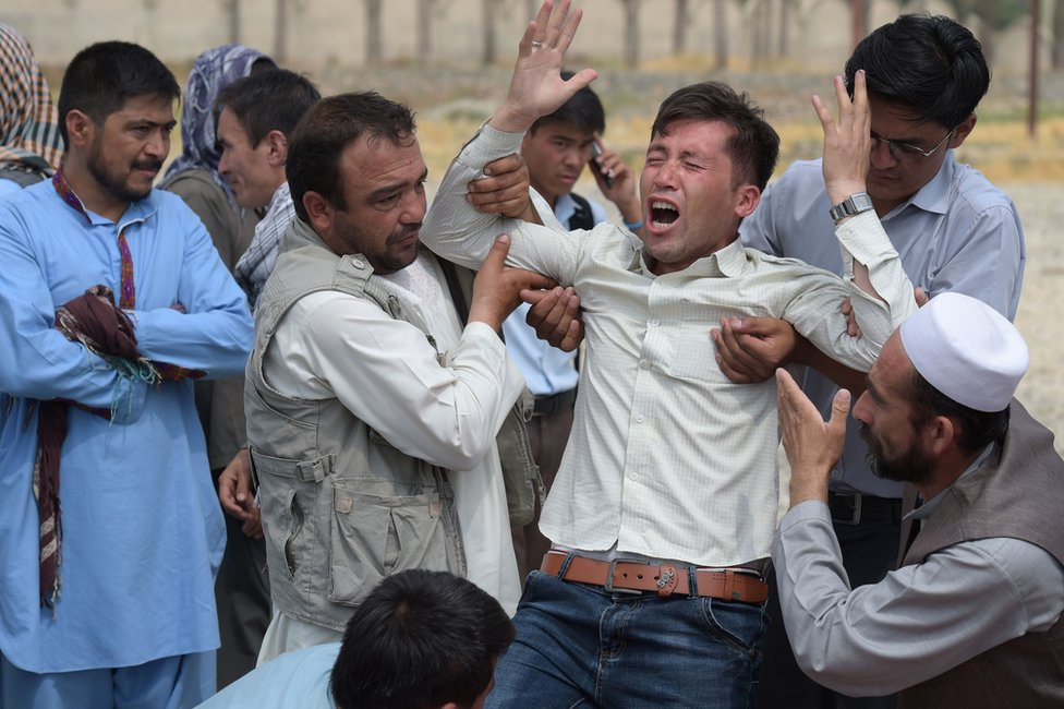 A relative (C) is comforted as he weeps alongside unseen shoes and other belongings of those who were killed in the twin suicide attack, at a mosque in Kabul, 24 July