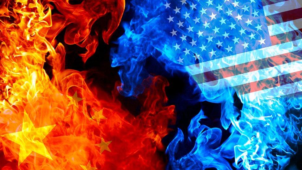 Banderas de China y Estados Unidos quemándose.