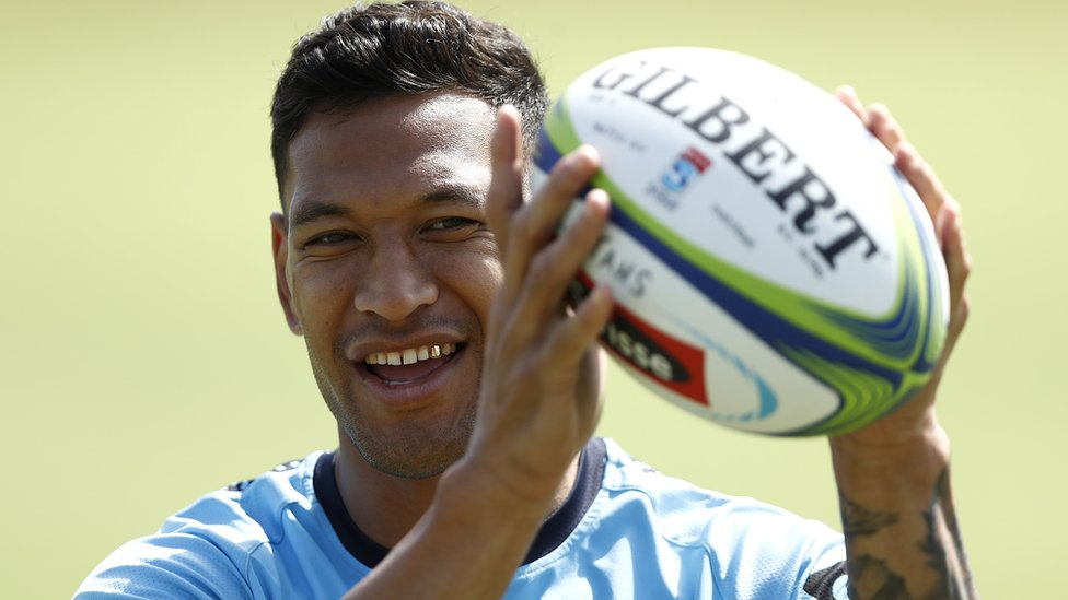 Israel Folau smiles as he catches a rugby ball
