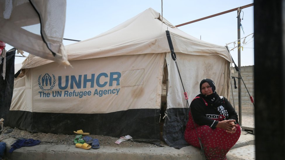 A displaced Iraqi woman sits outside a tent where she is taking shelter in a camp for internally displaced people.