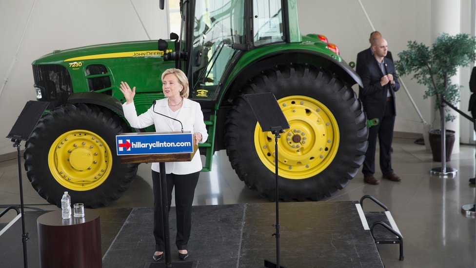 Hillary Clinton speaks in front of a tractor