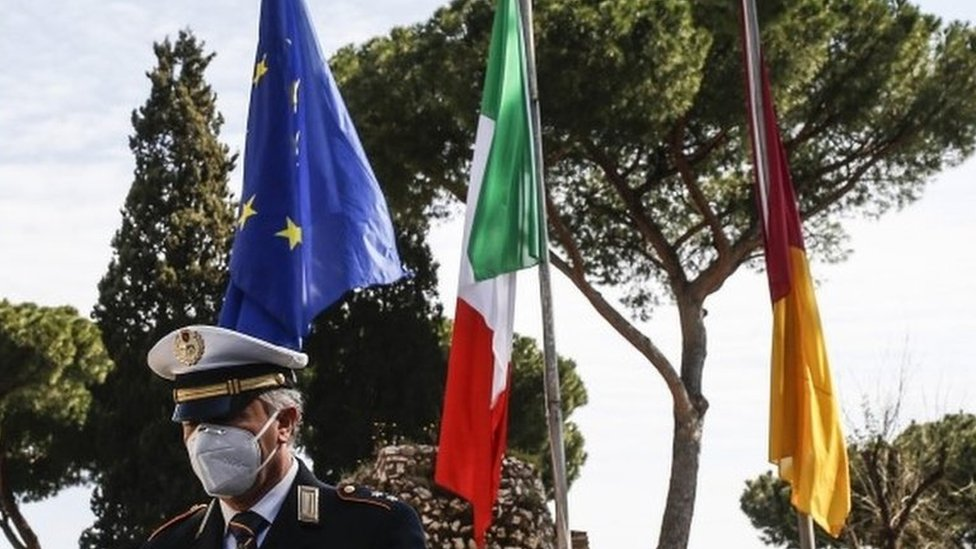 An Italian police officer stands next to EU, Italian and German flags in Rome. Photo: 31 March 2020