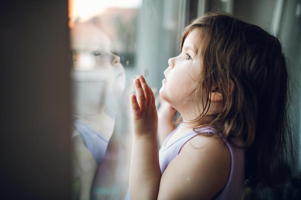 طفلة تنظر عبر نافذة وترى صورتها منعكسة