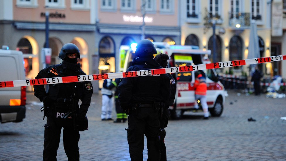 Police officers and forensic investigators and an ambulance work at one of the scenes in Trier