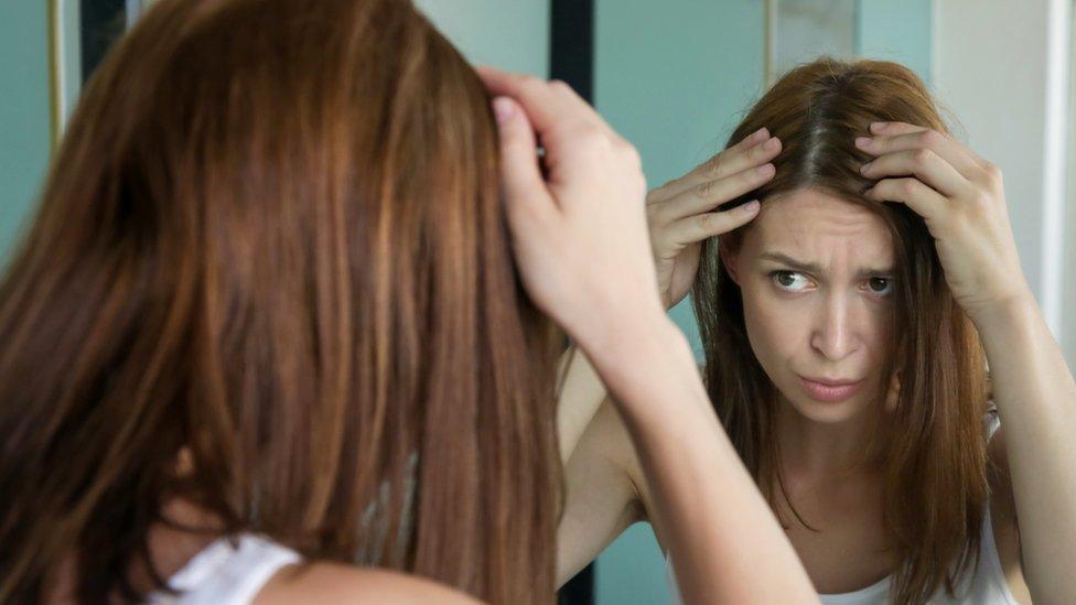 Mujer mirándose las canas en el espejo