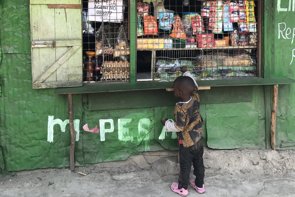 Young boy standing in front of M-Pesa agent shop