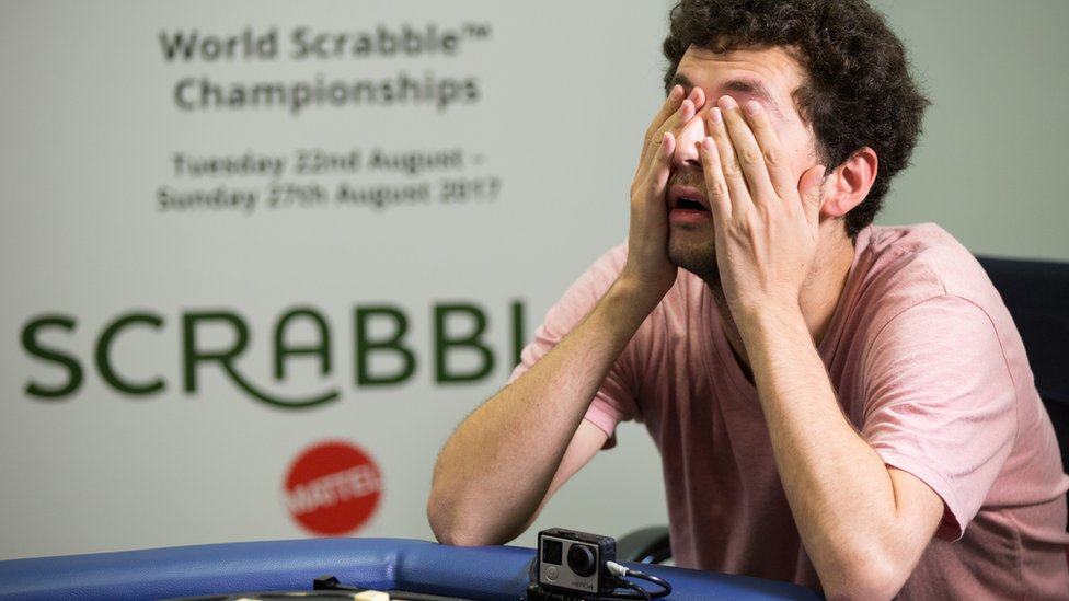 David Eldar covers his eyes playing scrabble