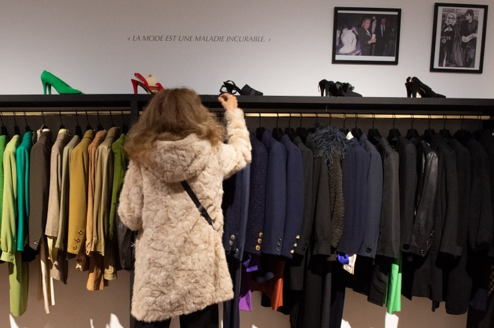 Racks of suit jackets arranged by shade