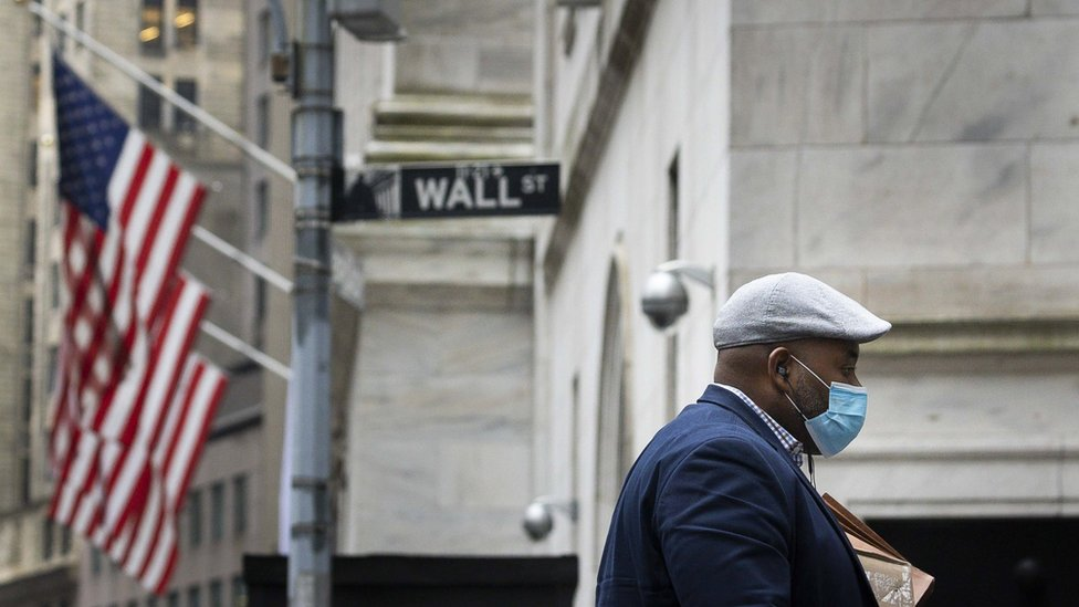 man with mask walks past Wall Street sign