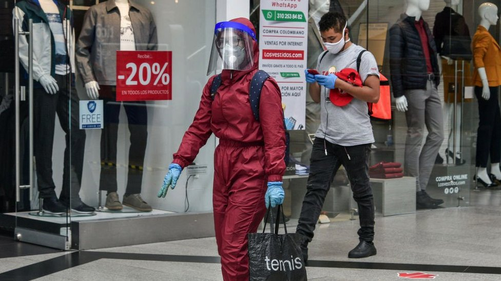 A woman wearing a biosafety suit walks holding a shopping bag at the Unicentro shopping center in Bogota, Colombia on July 01, 2020.