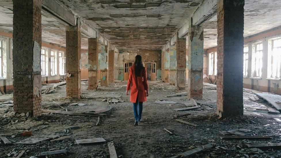mujer en edificio de Siria
