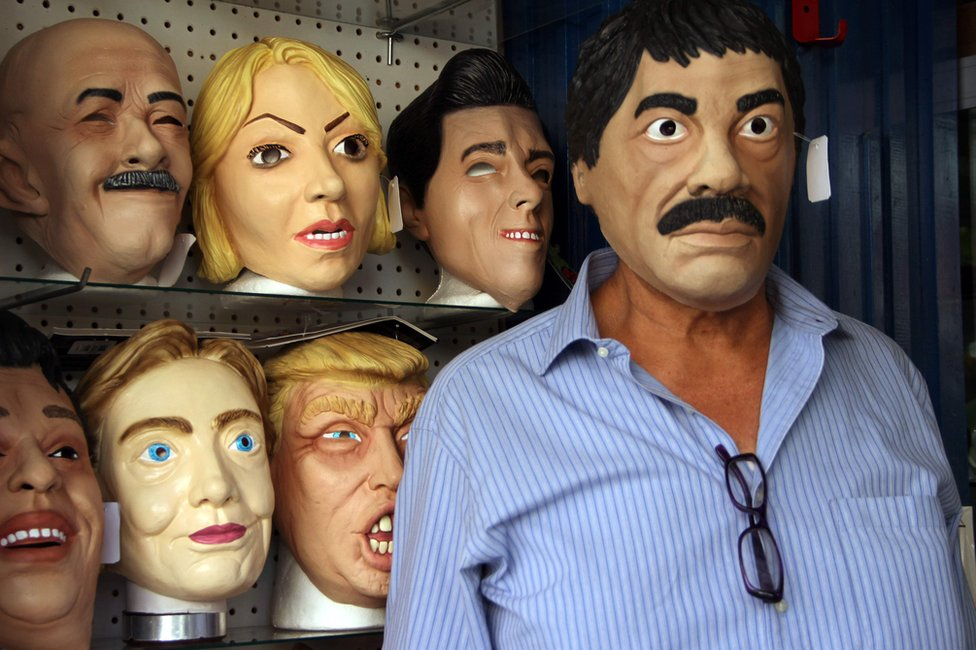 """Shopkeeper Manuel Robles (R) poses with a latex mask depicting Mexican drug trafficker Joaquin Guzman Loera -aka """"El Chapo""""- for sale for the upcoming Day of the Dead, in Ciudad Juarez, Chihuahua State, Mexico, 25 October"""