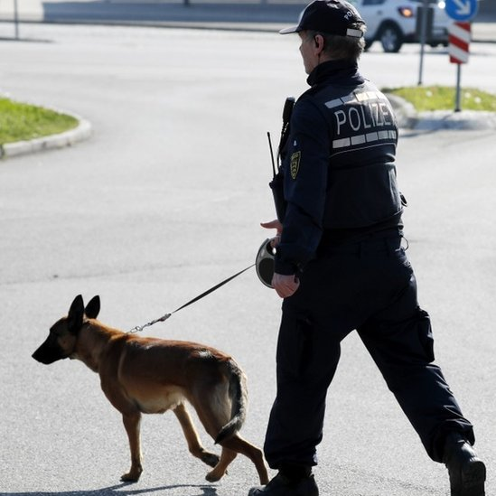 A police officer with his dog patrols in a street near the site where a suspect in the bombing attack on team bus of Borussia Dortmund was arrested, in Rottenburg (21 April 2017)