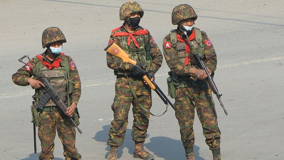 Soldados armados vigilan una manifestación.