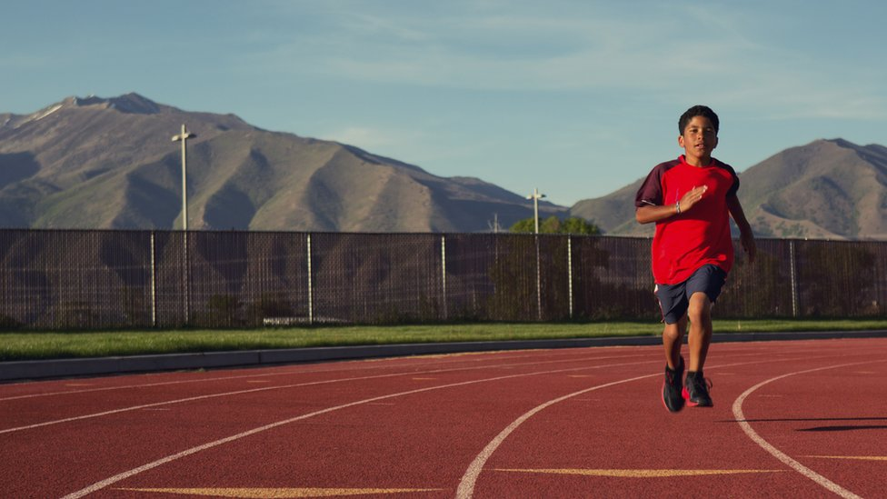 A child runs on a track