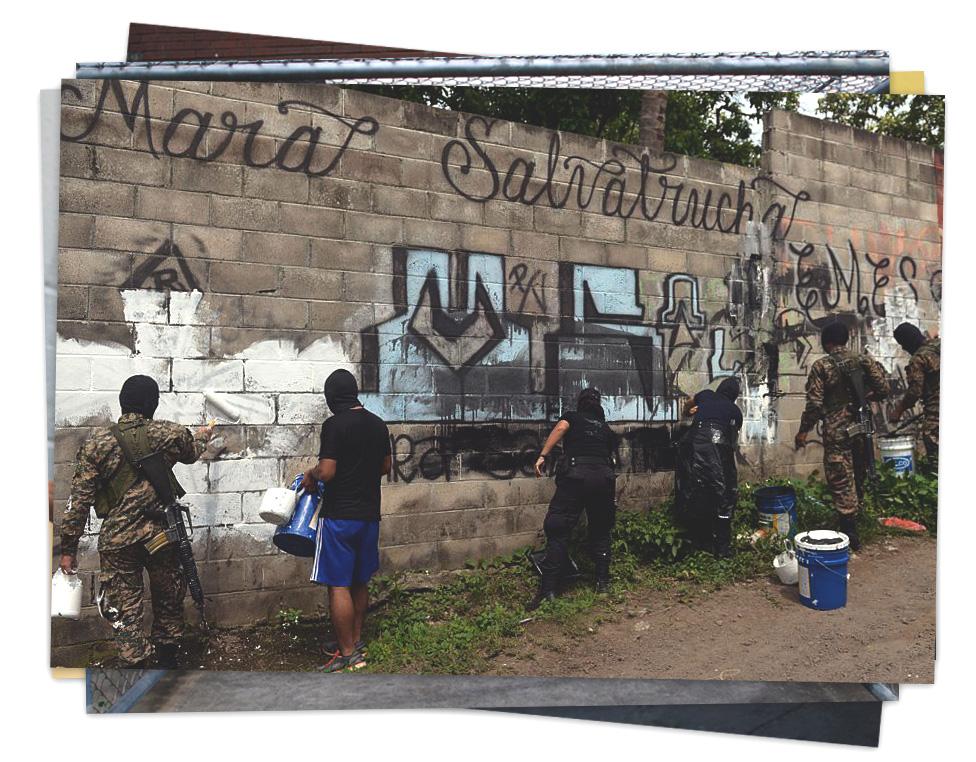 Un grupo de funcionarios tapa un grafiti de la MS-13 con pintura en un poblado de El Salvador
