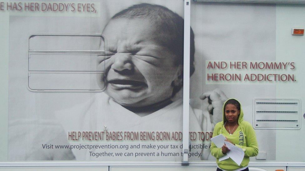 Mujer de pie al lado de un camión.