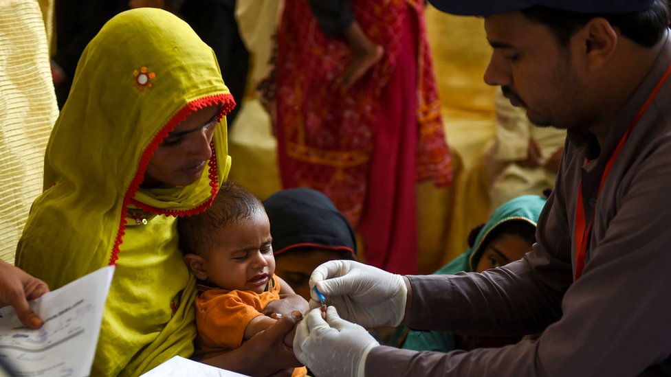 A mother holds her child, who is tested for HIV