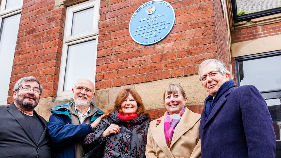 Five people standing below a blue plaque, which is on a building wall