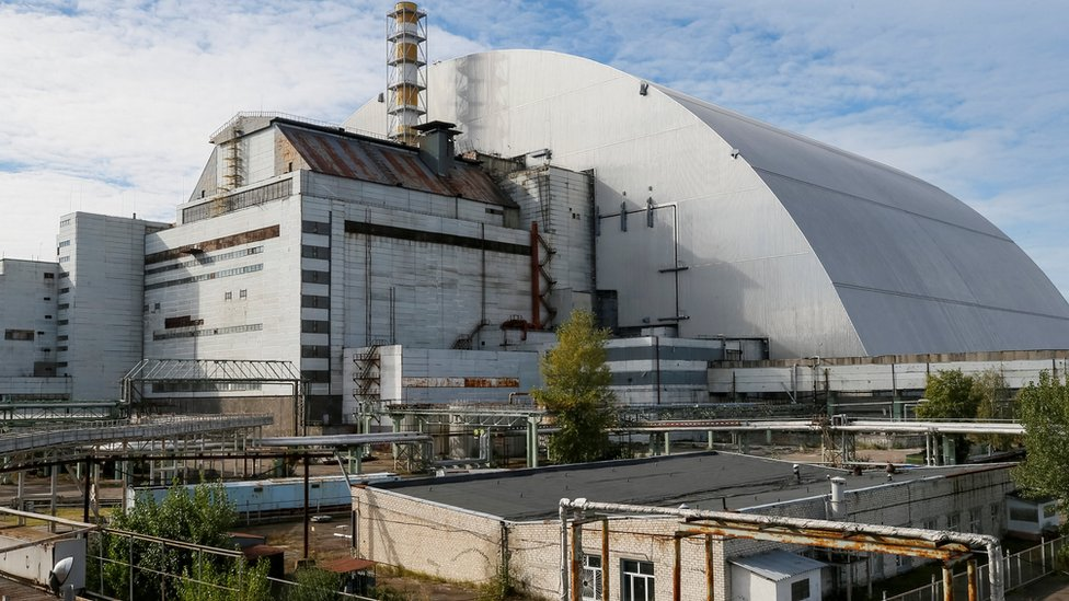 A new Safe Confinement arch covers the damaged fourth reactor of the Chernobyl nuclear power plant near a newly built solar power plant in Chernobyl