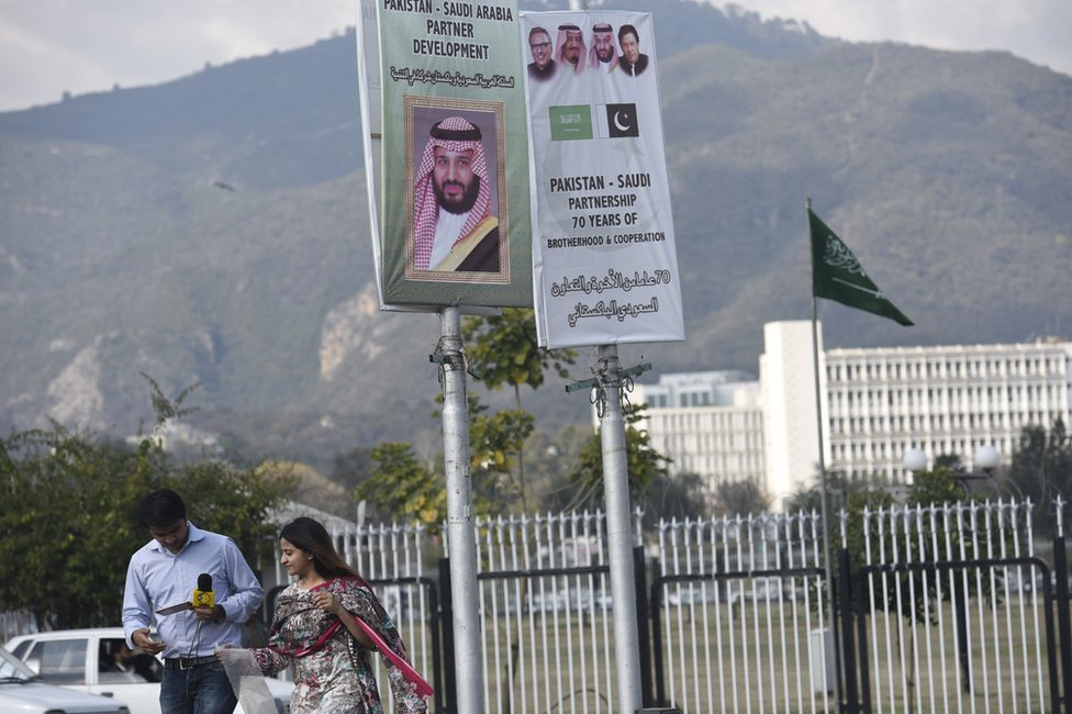 "Reporters walk under a sign saying ""Pakistan-Saudi Arabia partner development"" and a picture of Mohammad Bin Salman"